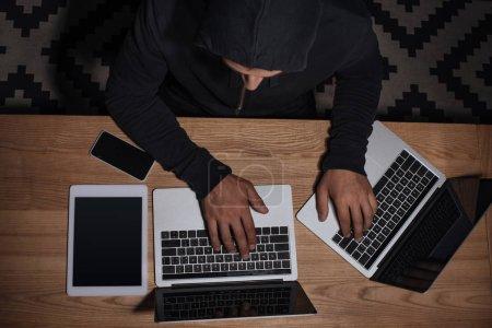 Foto de Vista aérea de hacker negro con capucha usando computadoras portátiles en el tablero con tablet y smartphone, concepto de la seguridad de cyber - Imagen libre de derechos