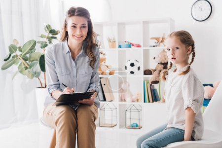 Photo for Smiling psychologist with clipboard sitting in office with little child and looking at camera - Royalty Free Image
