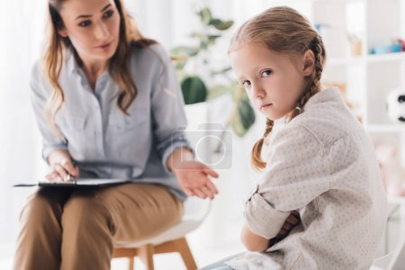 psychologist talking to angry child with crossed arms while she looking at camera