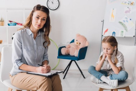 Photo for Adult psychologist with clipboard sitting near little depressed child in office and looking at camera - Royalty Free Image