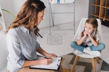 adult psychologist with clipboard sitting near little depressed child in office