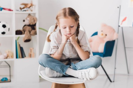 lonely little child sitting on chair in front of shelves with toys and looking down
