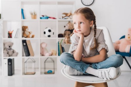 lonely little child sitting on chair in front of shelves with toys and looking at away