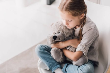 Photo for High angle view of depressed little child embracing her teddy bear - Royalty Free Image