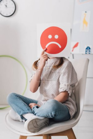 little child sitting on chair and covering face with sad face symbol