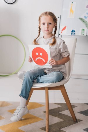 lonely little child sitting on chair holding sad face symbol