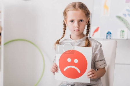 close-up portrait of lonely little child holding sad face symbol