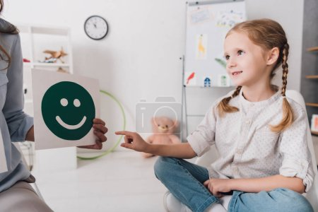 Photo for Adorable little child pointing at smiley face on paper in hand of psychologist - Royalty Free Image