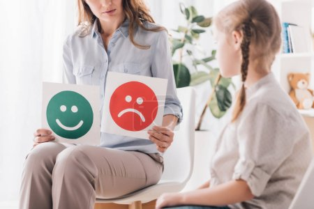 cropped shot of psychologist showing happy and sad emotion faces cards to child