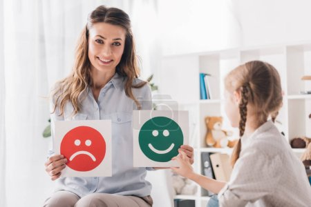 Photo for Smiling psychologist showing happy and sad emotion faces cards to child - Royalty Free Image