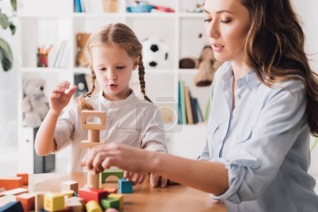 mother playing wooden blocks with little daughter