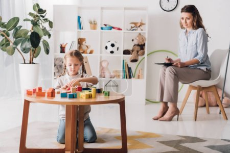 little child playing with blocks while psychologist sitting blurred on background