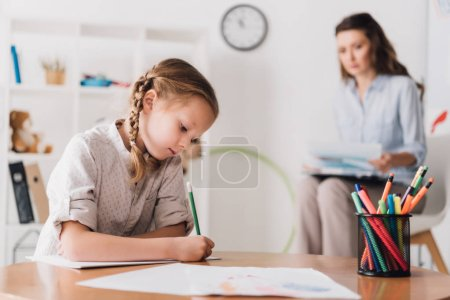 serious little child drawing while psychologist sitting blurred on background