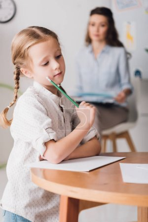 thoughtful little child drawing while psychologist with clipboard sitting blurred on background