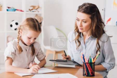 Photo for Adult psychologist sitting near child drawing with color pencils - Royalty Free Image