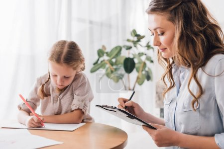 adult psychologist writing in clipboard while sitting near little drawing child
