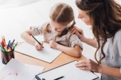 high angle view of psychologist with clipboard sitting near little child while she drawing with color pencils