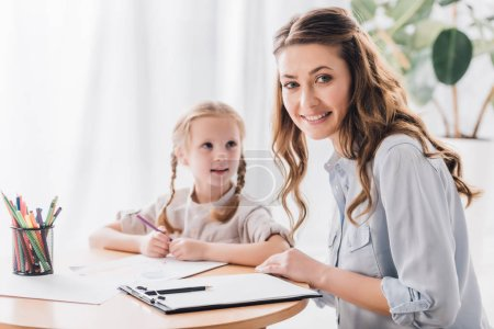 smiling psychologist with clipboard sitting near little child while she drawing with color pencils and looking at camera