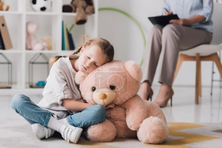 lonely little child with teddy bear sitting on floor with psychologist sitting on background