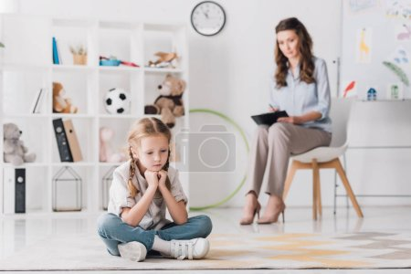 depressed little child sitting on floor with psychologist sitting on background