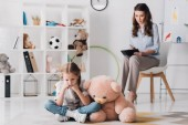 depressed little child with teddy bear sitting on floor with blurred psychologist sitting on background