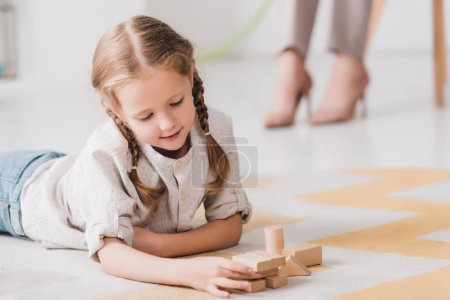 little child playing with wooden blocks on floor with blurred psychologist sitting on background