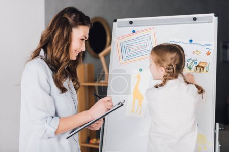 happy psychologist with clipboard talking to child near whiteboard with various drawings