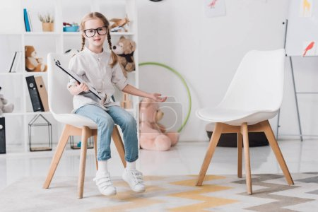 adorable little child in eyeglasses with clipboard sitting on chair and looking at camera