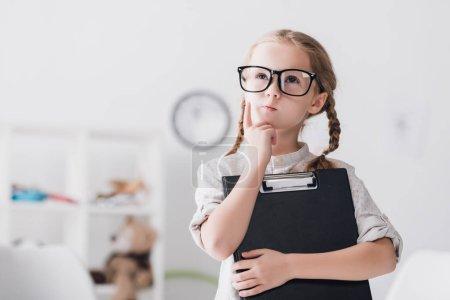 Photo pour Petit enfant réfléchi dans des lunettes avec presse-papiers regardant vers le haut - image libre de droit