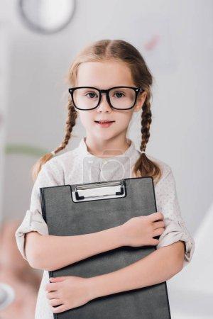 Photo pour Petit enfant souriant dans des lunettes avec presse-papiers regardant la caméra - image libre de droit