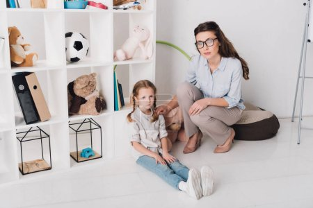 female psychologist supporting depressed child while she sitting on floor and looking at camera