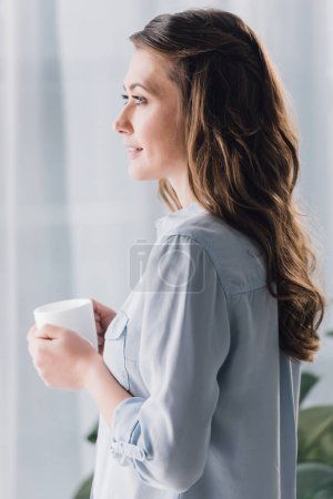 Photo for Side view of happy adult woman holding cup of warming beverage and looking away - Royalty Free Image