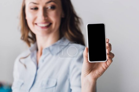 close-up portrait of happy adult woman in shirt showing smartphone with blank screen at camera