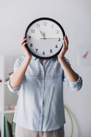 close-up portrait of woman in shirt covering face with clock