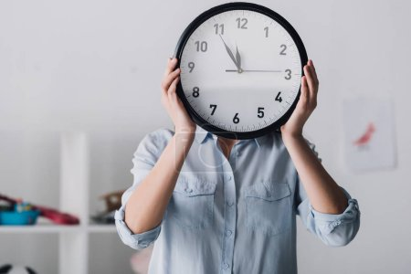 Photo for Close-up portrait of woman covering face with clock - Royalty Free Image
