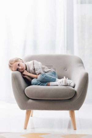 depressed little child lying in armchair alone