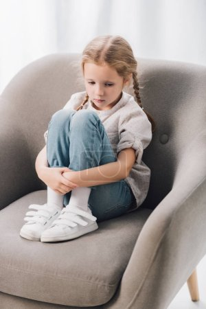 lonely little child sitting in armchair and looking down