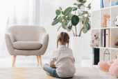 rear view of little child sitting on floor of empty room