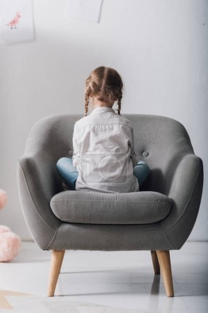 rear view of lonely little child sitting in armchair in front of white wall