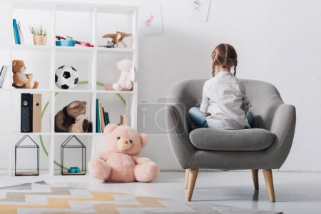 rear view of lonely little child sitting in armchair in front of shelves with toys
