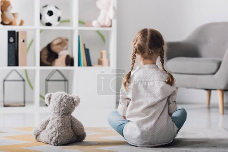 rear view of little child in white shirt sitting on floor with teddy bear