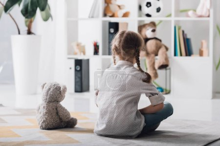 rear view of lonely little child sitting on floor with teddy bear
