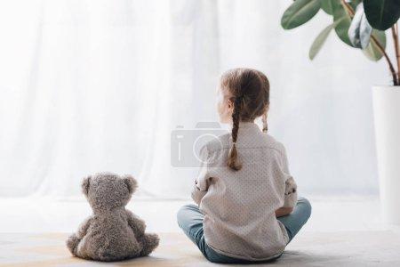 Photo pour Vue arrière du petit enfant assis sur le sol avec un ours en peluche et regardant ailleurs - image libre de droit