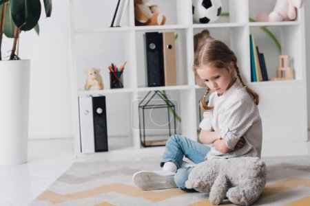 depressed little child sitting on floor with teddy bear
