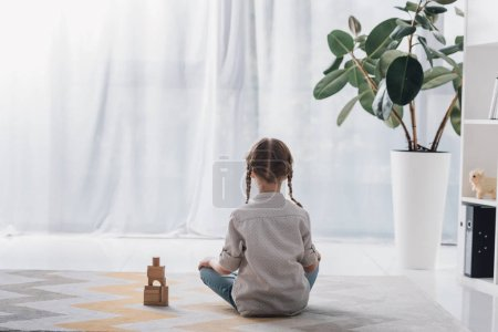 rear view of little child sitting on floor with wooden blocks and looking away