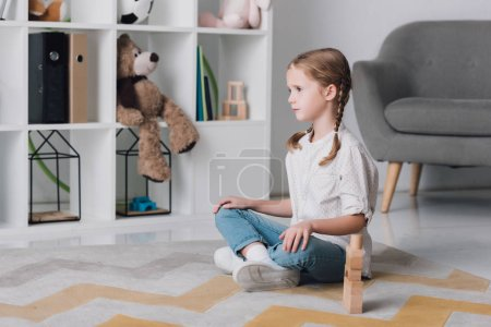 depressed little child sitting on floor with wooden blocks and looking away