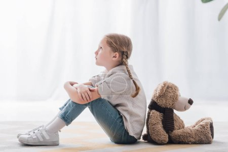 side view of thoughtful little child sitting on floor back to back with teddy bear