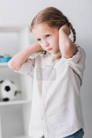 close-up portrait of depressed little kid covering ears with hands and looking away