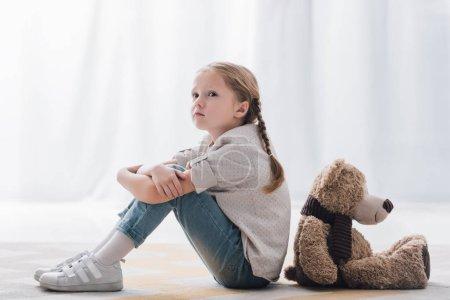Photo pour Vue latérale du déprimé petit enfant assis sur le sol dos à dos avec ours en peluche - image libre de droit
