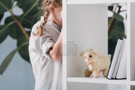 scared little child standing behind bookshelves and crying